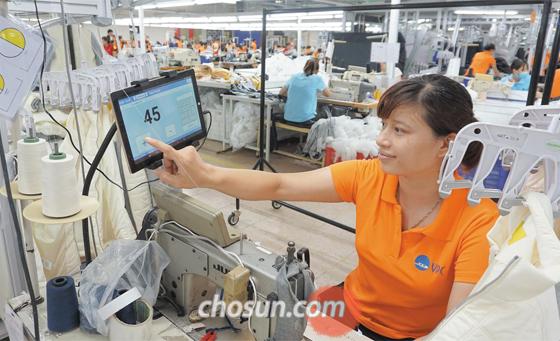 베트남 박닌성에 있는 태평양물산 생산 라인에서 현지 직원이 작업을 마무리한 뒤 태블릿PC 화면을 터치하고 있다. 현장 작업자가 입력한 숫자는 실시간으로 라인마다 있는 작업 현황 모니터와 본사, 공장 사무실로 전송된다.