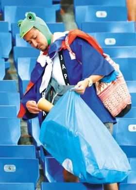 역전패 아픔이 가시기도 전, 한 일본 팬이 경기장 쓰레기를 수거하는 모습. 일본 관중의 청소 매너는 상대국 팬들의 자연스러운 동참을 이끌기도 했다.