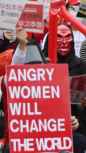 몰카 편파 수사 규탄 집회에 참석한 한 여성이 '분노한 여성이 세상을 바꾼다'는 뜻의 손 피켓을 들었다.