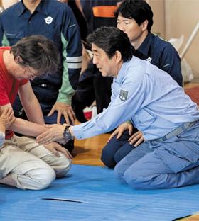 무릎 꿇은 아베 - 아베 신조(오른쪽) 일본 총리가 11일 폭우로 46명이 희생된 오카야마(岡山)현 구라시키(倉敷)시 마비초(眞備町)의 주민 대피소를 찾아 무릎 꿇고 이재민들을 위로하고 있다.