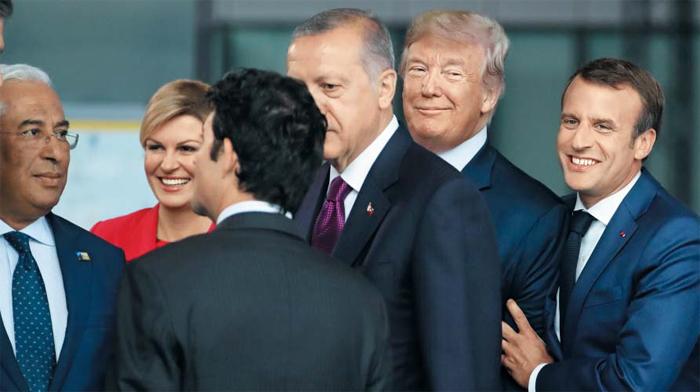 팔짱 낀 트럼프·마크롱 - 11일(현지 시각) 벨기에 브뤼셀에 있는 나토(북대서양조약기구) 본부에서 에마뉘엘 마크롱(맨 오른쪽) 프랑스 대통령이 도널드 트럼프 미국 대통령의 팔을 잡고 웃고 있다. 사진 왼쪽부터 안토니우 코스타 포르투갈 총리, 콜린다 그라바르키타로비치 크로아티아 대통령, 쥐스탱 트뤼도(뒷모습) 캐나다 총리, 레제프 에르도안 터키 대통령. 도널드 트럼프 미 대통령은 정상회의장에서 미국의 나토 탈퇴 가능성까지 거론하며 동맹국들의 방위비 증액을 강하게 요구했다.