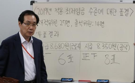 류장수 최저임금위원회 위원장이 14일 2019년 최저임금 결정 직후 투표 결과가 적힌 안내판을 지나가고 있다. /연합뉴스