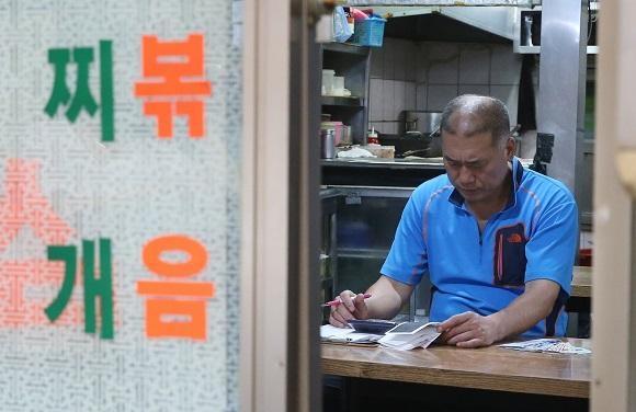 서울 종로3가의 한 식당 주인이 하루 영업을 마치고 텅 빈 식당에 앉아 계산기를 두드리고 있다. /조선일보DB