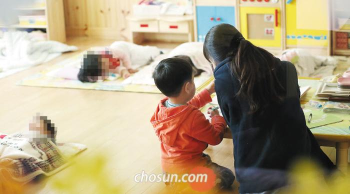 서울 성동구의 한 어린이집에서 보육교사가 낮잠 시간에 깨어 있는 아이를 돌보고 있다. 보육교사에게 의무 휴식 시간을 보장하는 법이 7월부터 시행되자 정부는 낮잠 시간을 교사 휴식시간으로 활용하라는 지침을 내렸다.