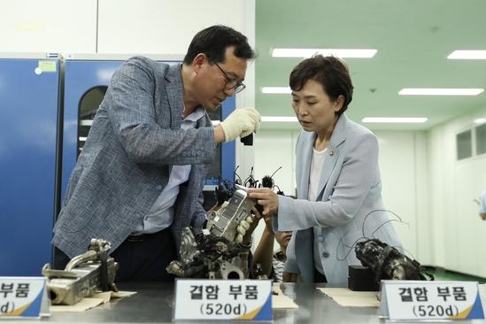 김현미 국토교통부 장관(사진 오른쪽)이 8일 경기도 화성시 자동차안전연구원에서 화재가 난 BMW 차량의 부품을 살펴보고 있다. /국토부 제공