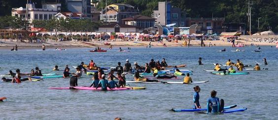 폭염이 기승을 부린 지난 5일 강원도 양양 죽도 해변이 파도타기를 즐기는 서퍼들로 붐비고 있다. /연합뉴스