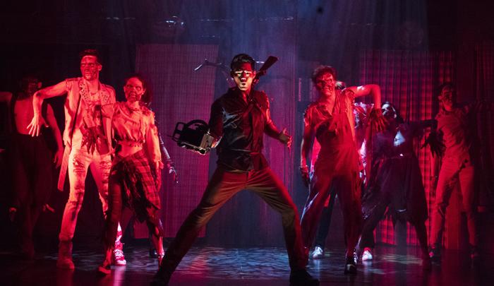뮤지컬 '이블 데드' 공연 중, 좀비에게 물린 손을 잘라내고 전기톱을 끼운 주인공 스캇(가운데)이 좀비들과 뒤섞여 춤추는 장면. 경쾌한 로큰롤 음악, 좀비와 인간이 뒤엉키는 군무, 욕설과 익살이 혼합된 B급 유머가 매력 포인트다.