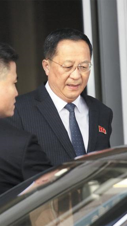 """이란 떠나 베이징 도착한 北리용호 - 리용호 북한 외무상이 10일 중국 베이징 서우두 공항에서 차량을 타기 위해 이동하고 있다. 리 외무상은 하루 전 이란 방문 중 """"핵 기술을 포기하지 않겠다""""고 말했다."""