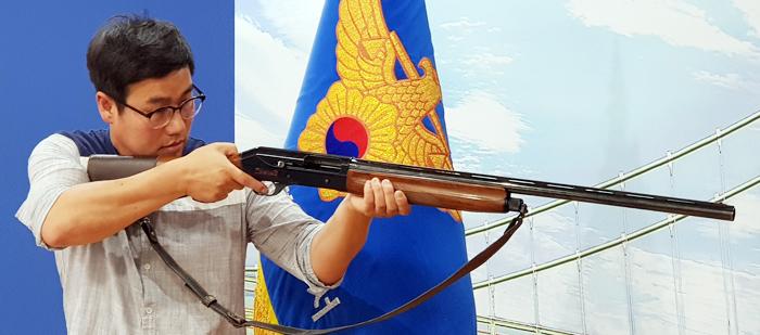 77세 노인이 사용했던 엽총 22일 경북 봉화경찰서에서 한 경찰관이 김모(77)씨가 면사무소 직원들을 쏠 때 사용한 엽총을 들고 범행을 시연하고 있다.