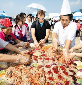 지난해 개최된 '춘천막국수닭갈비 축제'에서 참가자들이 막국수에 양념장을 비비며 시식 체험을 하고 있다.