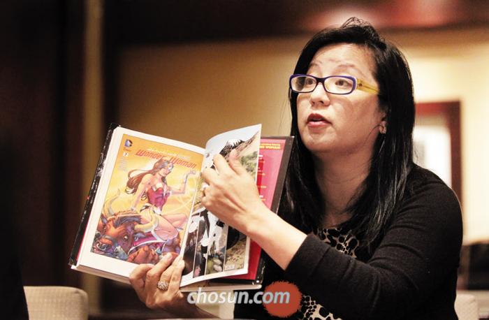 """지난 29일 만난 만화 스토리 작가 에이미 추가 2015년 DC 코믹스와 함께 작업한 '원더우먼' 만화책을 들어 보이고 있다. """"앞으로도 여성의 삶을 만화로 폭넓게 다루겠다""""고 했다."""