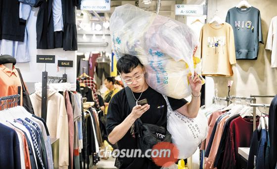 지난 5일 자정 서울 동대문시장의 한 도매 상가에서 스타트업 링크샵스 직원이 옷이 가득 담긴 비닐봉지를 어깨에 짊어진 채 나오고 있다.