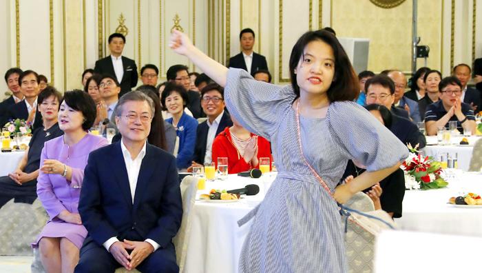 문재인 대통령이 12일 청와대 영빈관에서 열린 '발달 장애인 평생 케어 종합 대책 발표' 행사에서 발달 장애인 장혜정씨의 춤을 보며 웃고 있다.