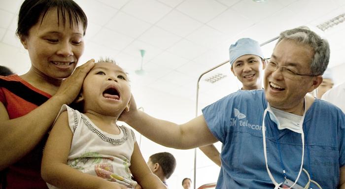 백롱민 교수가 지난 2009년 베트남 탄호아 의료 봉사 현장에서 수술받은 아이를 보며 웃고 있다.
