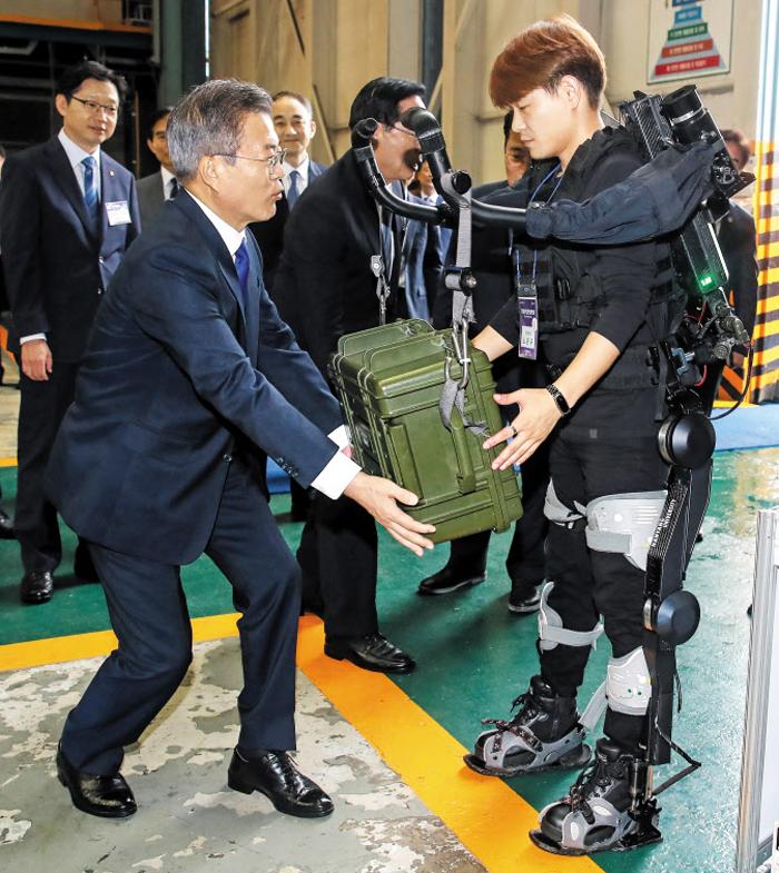 문재인 대통령이 14일 경남 거제시 대우조선해양에서 열린 4차 산업혁명 국방 기술 시연회에서 근력 로봇으로 들어 올린 가방 무게를 가늠해 보고 있다.