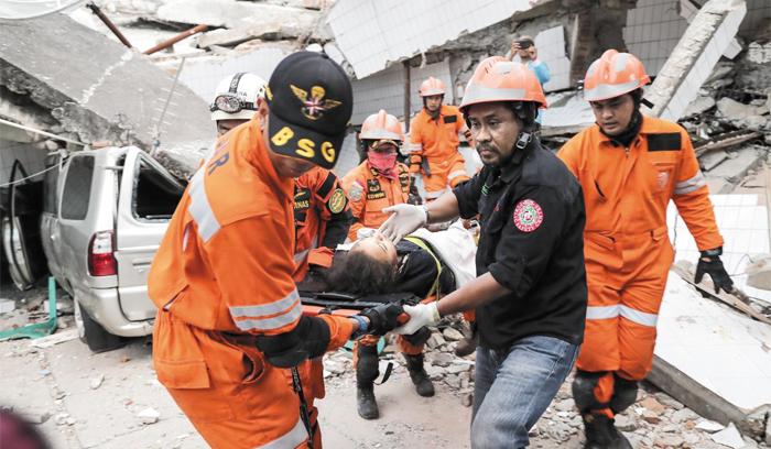 30일 인도네시아 술라웨시섬 팔루시 강진 현장에서 구조대원들이 생존자를 구해 옮기고 있다.