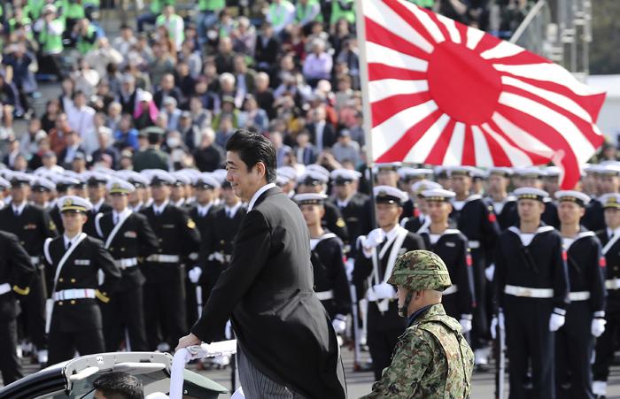 2016년 10월 열린 자위대 사열식에서 욱일기를 든 해군 앞을 지나가는 아베 신조 일본 총리.
