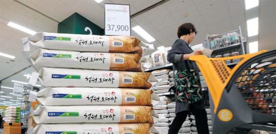 지난 1일 서울의 한 대형 마트에 장을 보러 온 고객이 쌀포대가 쌓여 있는 양곡 코너 앞을 지나가고 있다. 수년간 하락세를 보인 쌀값을 끌어올리기 위해 정부가 지난해 시장에서 쌀을 대거 사들이면서 올 들어 쌀값 급등세가 이어지고 있다.