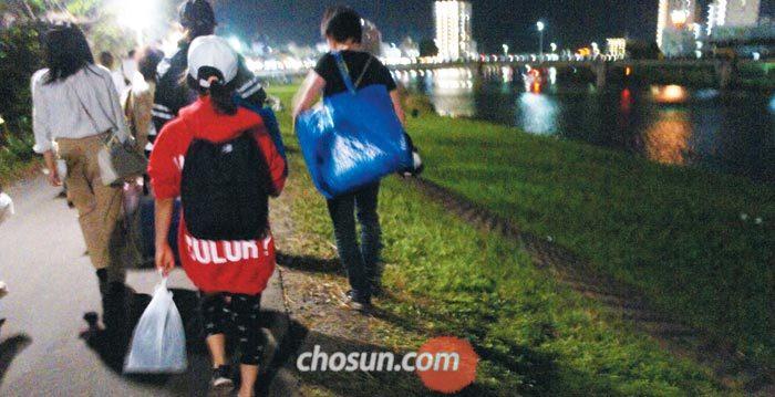 6일 밤 일본 3대 불꽃놀이 축제가 열린 이바라키현 쓰치우라(土浦)시 사쿠라강에서 시민들이 각자 자기가 만든 쓰레기를 한 손에 들고 귀가하고 있다.