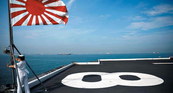 일본 해상자위대의 헬기 탑재 항공모함인'가가'에 탑승한 한 대원이 지난달 22일 인도양에서 훈련을 위해 출항하기 전 욱일기(旭日旗)를 게양하고 있다.