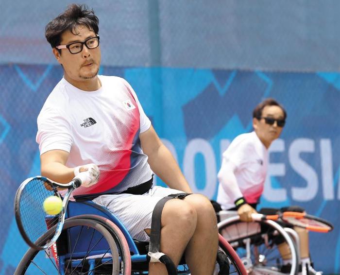 프로야구 두산 투수 출신인 김명제가 11일 열린 인도네시아 장애인 아시안게임 남자 휠체어 테니스 복식(쿼드부문) 일본과의 결승전에서 공을 받아 넘기는 모습. 은메달을 목에 건 김명제의 다음 목표는 패럴림픽에 나가 메달을 따는 것이다.
