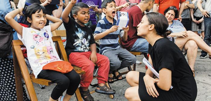 뉴욕 브롱코스·퀸즈 연방 하원 의원 민주당 후보로 출마한 알렉산드리아 오카시오-코르테스(오른쪽)가 지난 5월 뉴욕 엘름허스트의 선거사무소 개소식 행사 도중 어린이들의 이야기를 듣고 있다.