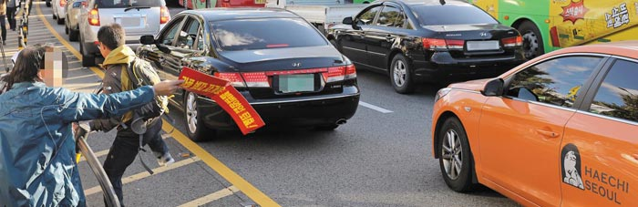 """카카오 카풀 서비스에 반대해 18일 운행 거부에 나선 한 택시 기사(왼쪽)가 영업 중인 다른 택시를 향해""""왜 동참하지 않느냐""""며 항의하고 있다."""