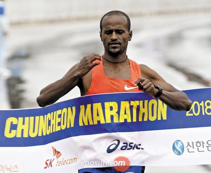 28일 열린 2018 춘천마라톤 1위를 차지한 아레도 쉬페라 탐루(에티오피아)가 결승선을 통과하는 모습.