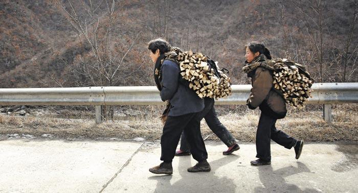 2016년 겨울 북한 황해도 신평군에서 여성들이 장작을 메고 걷고 있다. 북 지방 경제는 계속 어렵다고 한다.