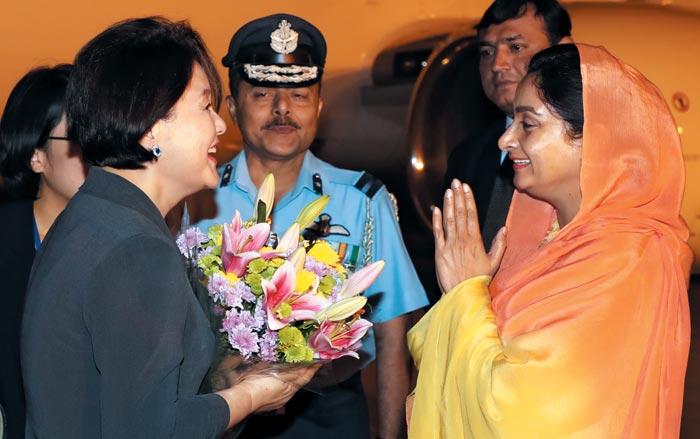 김정숙 여사가 4일 인도 뉴델리 팔람 공군 공항에 도착해 카우르 바달 인도 식품산업부 장관에게 꽃다발을 받은 뒤 인사를 나누고 있다.