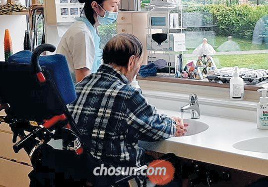 휠체어를 탄 한 일본 노인이 요양보호사의 도움으로 손을 씻고 있다.