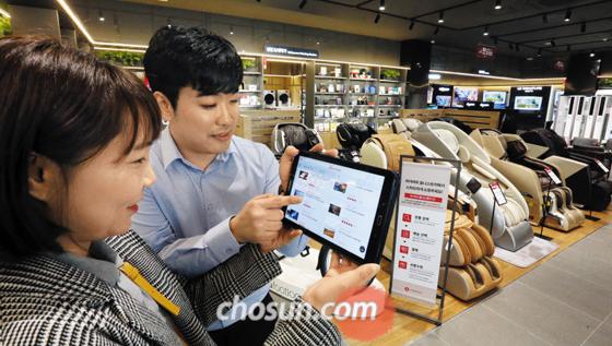 6일 경기 구리시 롯데하이마트 매장에서 한 여성 고객이 옴니 전용 앱이 내장된 태블릿 PC를 통해 가전제품을 검색하고 있다. 가전 매장에 수천권의 책을 갖춘 북카페를 결합한 이곳은 온·오프라인 경계를 넘는 '디지털 트랜스포메이션'의 현장이다.