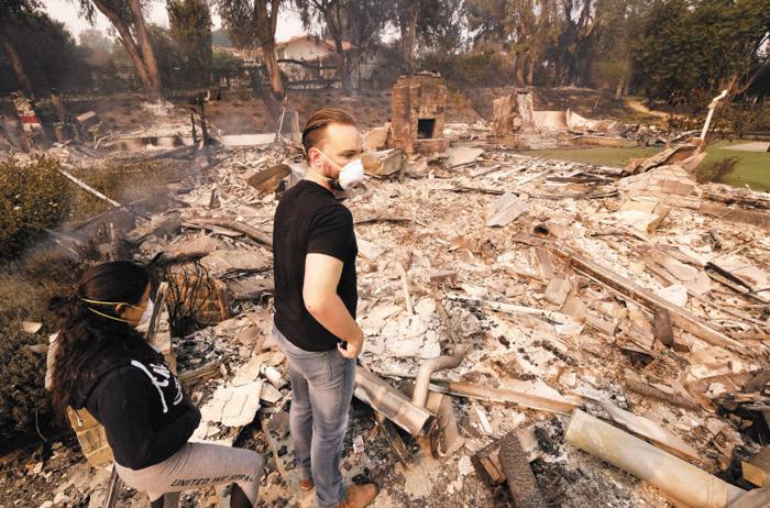 10일(현지 시각) 대형 산불이 휩쓸고 지나간 캘리포니아주(州) 말리부에서 한 남성과 그의 여자 친구가 잿더미로 변한 집을 바라보고 있다. 캘리포니아주에서 대형 산불 3개가 동시에 발생해 최소 25명이 숨지고 주민 30만명이 대피하는 등 큰 피해가 발생했다.
