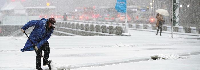 한 남성이 서울에 첫눈이 내린 지난 24일 서울 광화문광장에서 발목 높이까지 쌓인 눈을 치우고 있다.