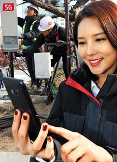 통신업체들이 5G 전파 송출을 시작한 1일 한 모델이 광화문에 설치한 5G 기지국에서 삼성 5G 스마트폰 시제품을 테스트하고 있다.