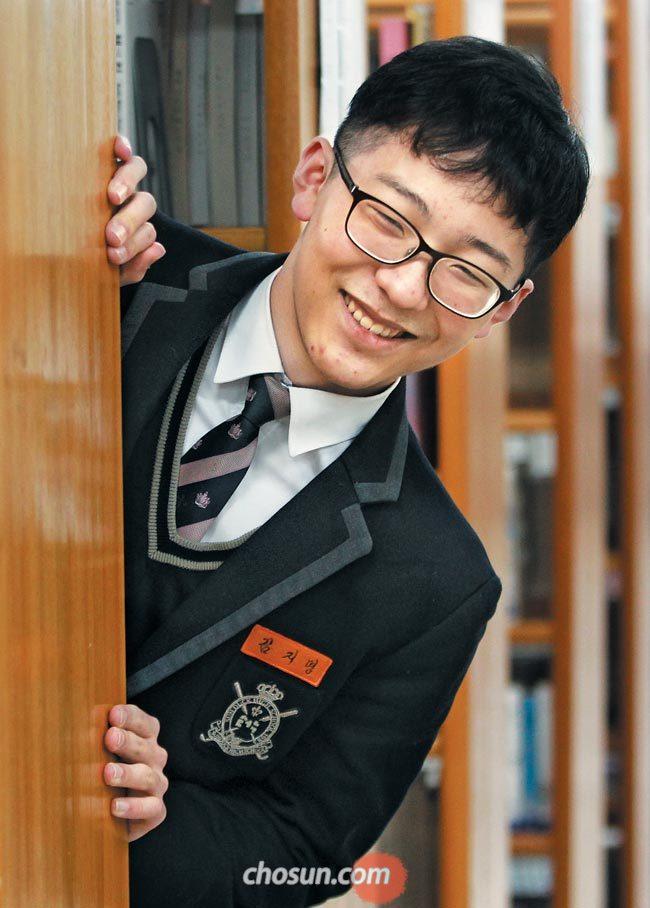 올해 수능 전 영역 만점을 받은 서울 선덕고 김지명(18)군이 4일 학교 도서관 책꽂이 사이로 얼굴을 내밀고 있다.