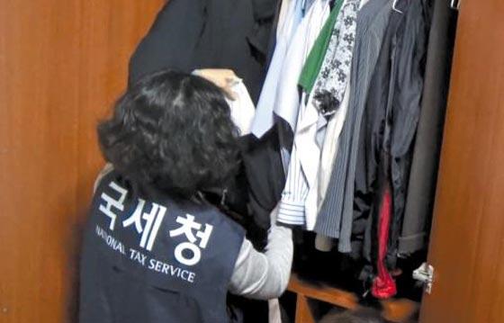 국세청 조사관이 재산 은닉 혐의를 받는 한 체납자의 옷장을 수색하고 있다. 옷장 속 양복 주머니에서는 100만원짜리 수표 180장(1억8000만원)이 발견됐다.
