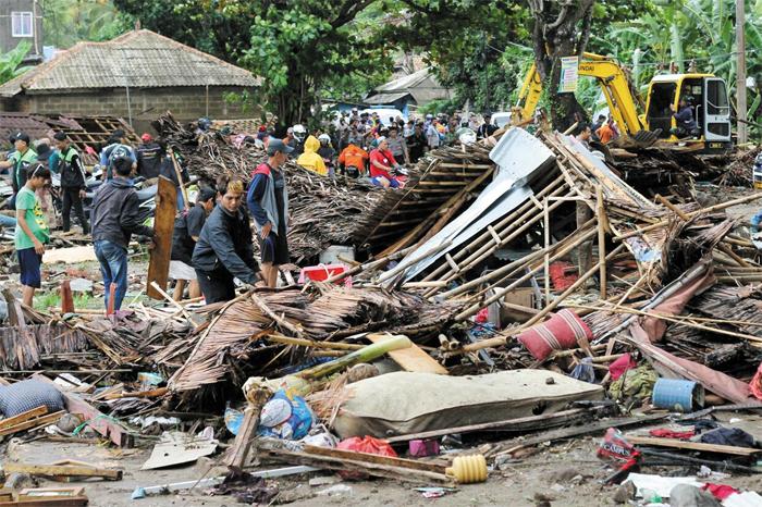 23일 인도네시아 자바섬의 판데글랑군(郡) 카리타 지역 주민들이 쓰나미로 폐허가 된 집터 잔해를 살펴보고 있다. 인도네시아 국가재난방지청은 자바섬과 수마트라섬 사이 순다해협에서 22일 쓰나미가 발생해 해안을 덮쳐 최소 222명이 숨지고, 843명이 부상했다고 밝혔다. 전문가들은 순다해협의 아낙 크라카타우 화산섬이 분화하며 해저에서 산사태가 나는 바람에 쓰나미가 난 것으로 보고 있다.