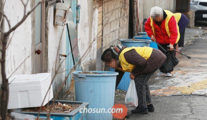 서울 노원구 중계동 백사마을 골목에서 노인들이 쓰레기 등을 줍고 있다.
