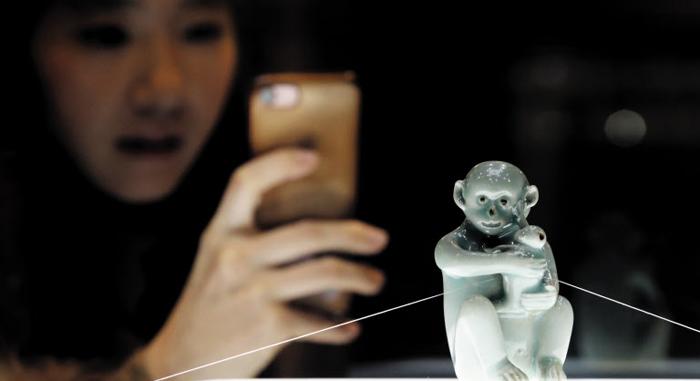 전시 개막을 하루 앞둔 3일 한 여성이 '청자모자원숭이형연적'을 사진 촬영하고 있다.