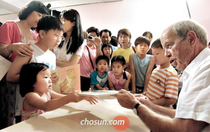 """2005년 서울에 온 존 버닝햄이 아이들 그림책에 사인해주며 """"감사합니다""""라고 말하는 모습."""