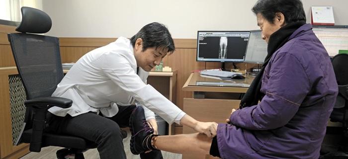 궁윤배(왼쪽) 세란병원 인공관절센터 부장에게 진료를 받는 심영세 씨의 모습 .