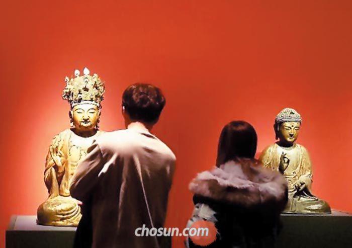 서울 용산 국립중앙박물관에서 열리고 있는'대고려, 그 찬란한 도전'에 전시된 고려 14세기 건칠보살좌상(왼쪽)과 금동아미타불좌상을 관람객들이 보고 있다.