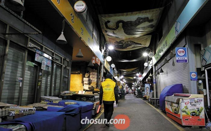 8일 새벽 서울 종로구 통인시장에서 전통시장 안전지킴이 김모(75)씨가 경광봉을 들고 가게 문이 닫힌 시장 거리를 돌아다니고 있다.