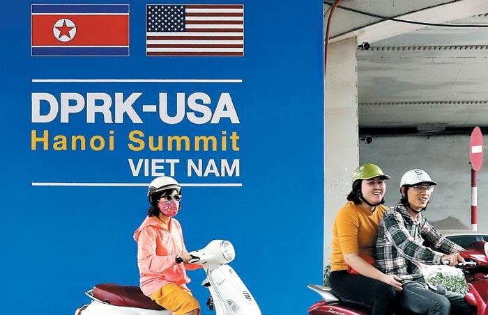 19일 베트남 수도 하노이 거리에서 오토바이를 탄 시민들이 제2차 미·북 정상회담 광고판을 지나가고 있다.