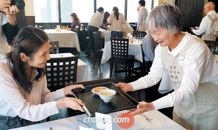 5일 일본 도쿄 후생노동성 청사 식당에서 치매 노인인 혼포(오른쪽 서 있는 사람)씨가 주문받은 음식을 고객에게 전달하고 있다