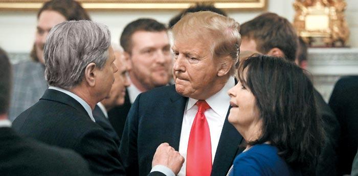 도널드 트럼프(가운데) 미 대통령이 4일(현지 시각) 백악관에서 공화당 존 호븐 연방 상원의원(노스다코타주·왼쪽)과 그의 아내 마이키 호븐(오른쪽)과 대화하고 있다.