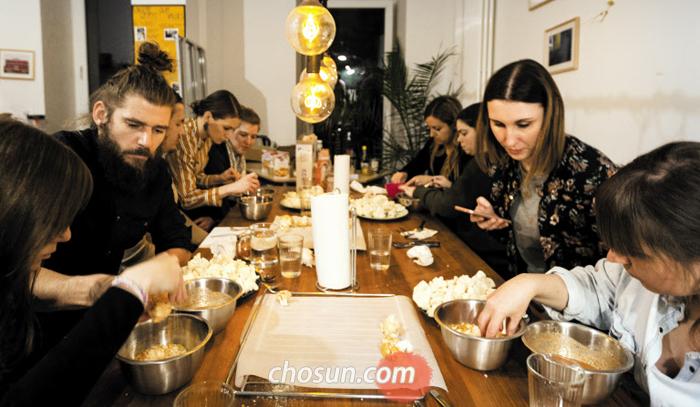 베를린에서 열린 채식 요리 수업에서 다국적 수강생들이 컬리플라워 구이를 만들고 있다.