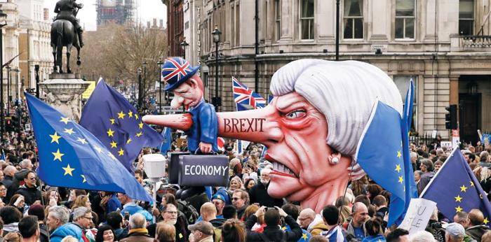 유럽연합 잔류를 원하는 영국 국민이 23일 런던 시내에서 연 시위에 테리사 메이 총리의 얼굴을 본뜬 거대 모형이 등장했다. 메이 총리의 길어진 코는 피노키오처럼 브렉시트와 관련해 계속 말을 바꾸며 혼란을 키운 정치권의 '거짓말'을 상징하며, 이러한 브렉시트 대혼란이 경제(Economy)를 뜻하는 영국 신사의 몸을 꿰뚫는 모습을 형상화했다.