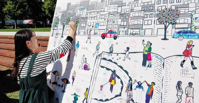 지난해 열린 부천 북페스티벌에 참여한 한 주민이 도심을 묘사한 캔버스를 채우는 모습.